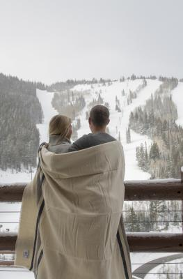 Couple wrapped in a blanket on Flagstaff deck at Stein Eriksen Lodge