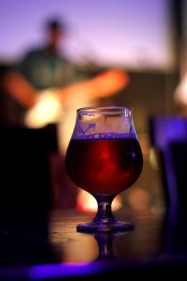 image of a beer with performing on stage in the background out of focus.
