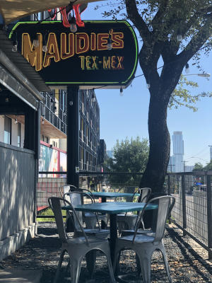 Patio with two tables and chairs below a neon sign reading Maudie's Tex-Mex. There is a tree and part of the downtown Austin skyline in the background