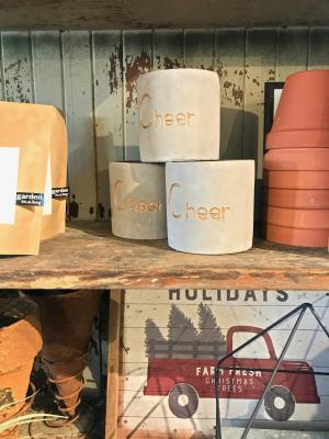 "Planters labeled ""Cheers"" on a shelf"