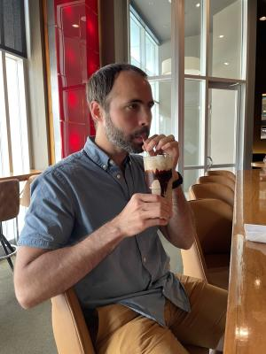 A man sips a milkshake at DLUX