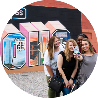 Group of Gals taking a selfie in front of the Greetings from OKC mural.