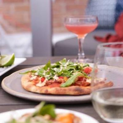 A photo of a small pizza and a cocktail in the background