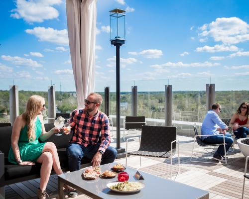 Couple cheersing drinks in a cabana on VASO's rooftop patio