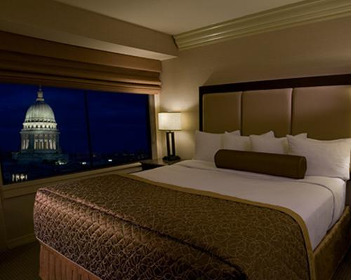 A king bed with a view of the State Capitol at the Madison Concourse Hotel and Governors Club