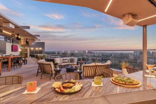 Image of a charcuterie board, a pizza topped with greens and two cocktails placed on top of the bar at Parkestry. In the background are lounge seating options and a view of the Anaheim skyline.