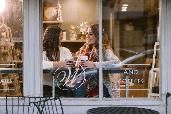 Two friends enjoying a cup of coffee in the window of Winans chocolate and coffees in Historic Dublin