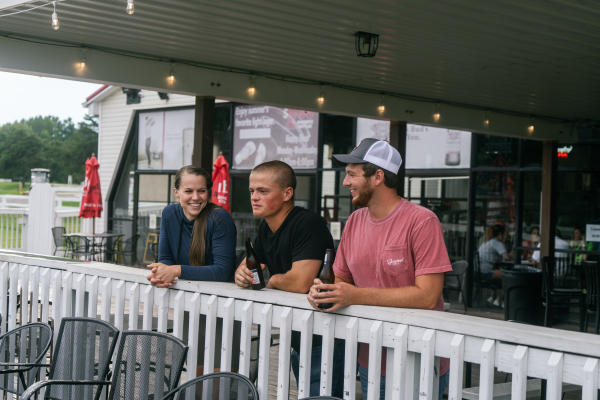 A group of friends enjoying a beer on the deck of Heartland Sports Pub