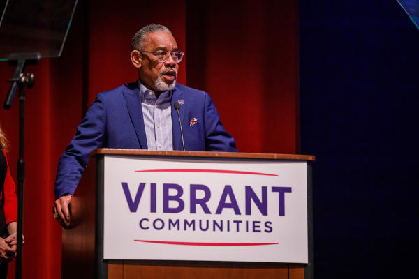 Arvis Dawson stands behind a podium that has a sign that says Vibrant Communities