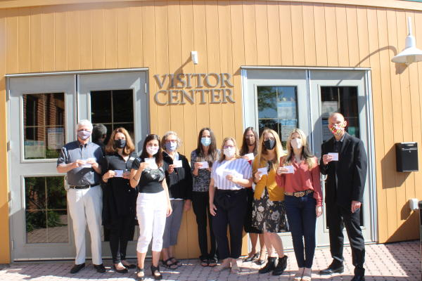 Visit Frederick staff standing in front of the Frederick Visitors Center with masks holding vaccine cards