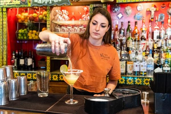 Woman Pouring A Drink At Under The Volcano In Houston, TX