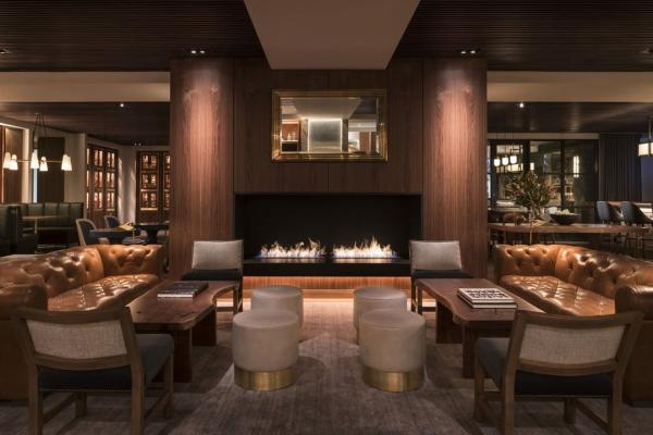A lounge with a fireplace in Bayou & Bottle at the Four Seasons Houston