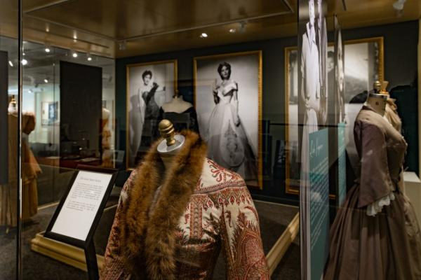 Costumes on exhibit in front of large pictures of Ava Gardner