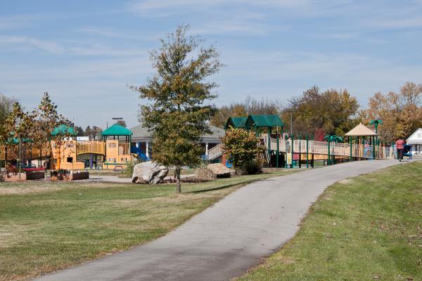 A paved trail and manicured lawn surround the play area at Knoxville's Caswell Park.