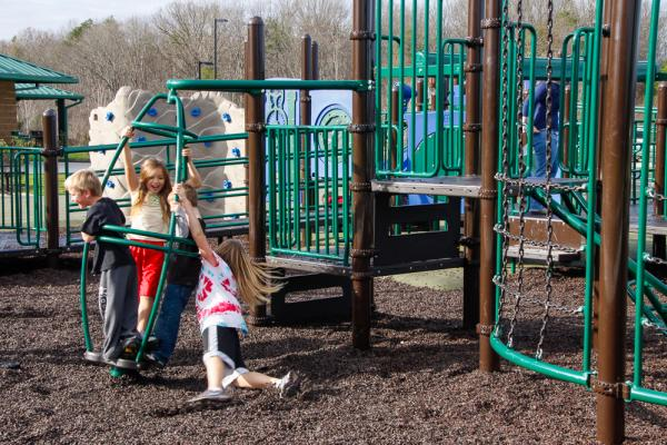 Children at McFee Park laugh as they enjoy the playground equipment.