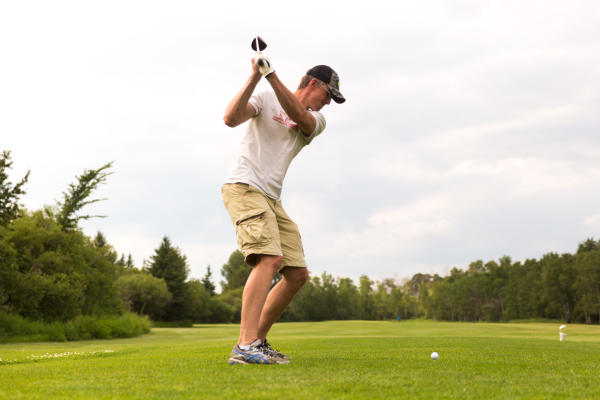 Golfer teeing off at Central Manitoba Golf Course