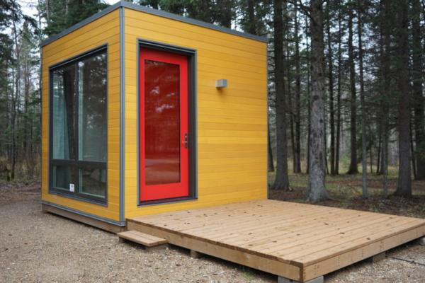 Micro cube cabin with red door at Riding Mountain National Park