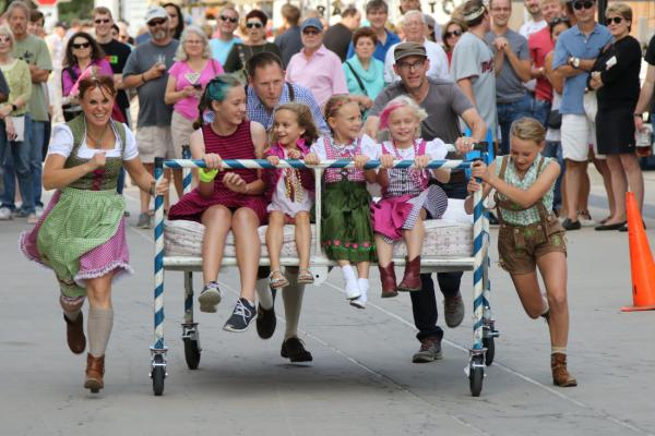 Children dressed in traditional German outfits sit in a cart being pushed by their parents at the St. Paul Oktoberfest