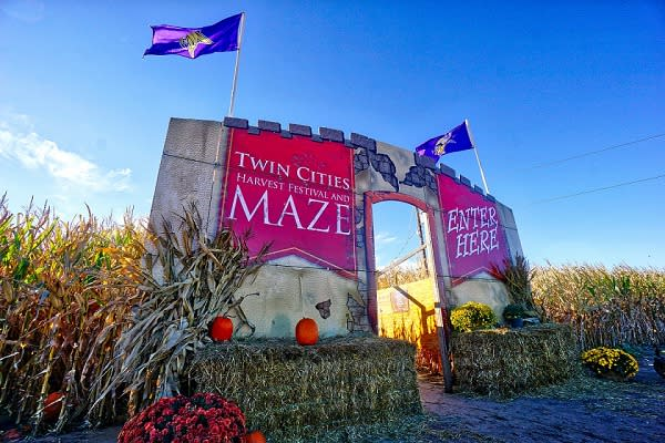 """A castle-like façade surrounded by hay bales says """"Twin Cities Harvest Festival and Maze. Enter Here"""""""