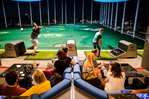 Young people swinging golf clubs at Topgolf