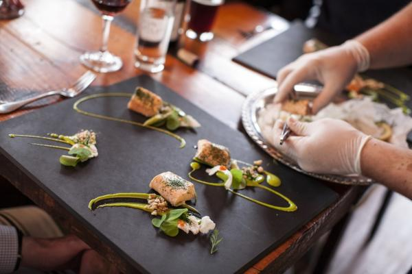 A chef prepares a plate of seafood and greens at Travail Kitchen in Robbinsdale, MN