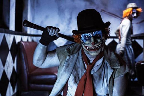 A scary looking clown wearing a dirty suit and holding a baseball bat staring at the camera in a photo from a Haunted House in Minneapolis