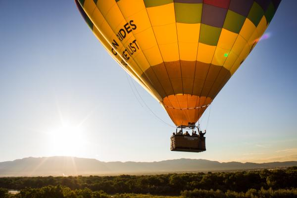 A hot air balloon floating with views of the mountains in the background