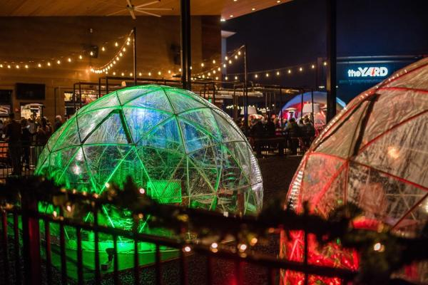 Picture of outdoor snowglobes at Farm Brew Live 2 Silos Brewing Company campus.  Snow globes can be rented for guests to stay warm during the holidays.  The snow globes are lit with green and red lights.