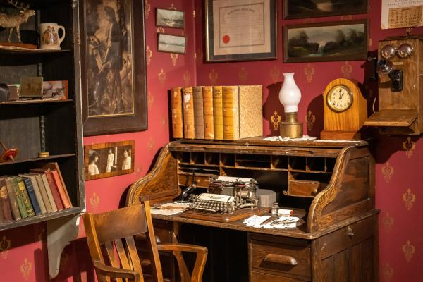 a museum exhibit of an early 20th century office, featuring a type-writer on a wooden desk