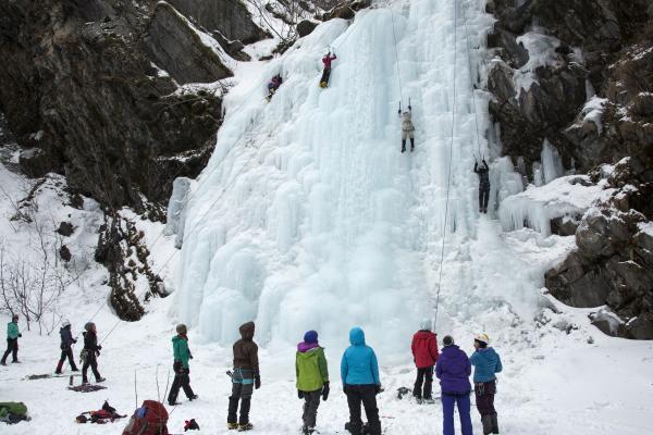 ice climbers climbing a frozen waterfall