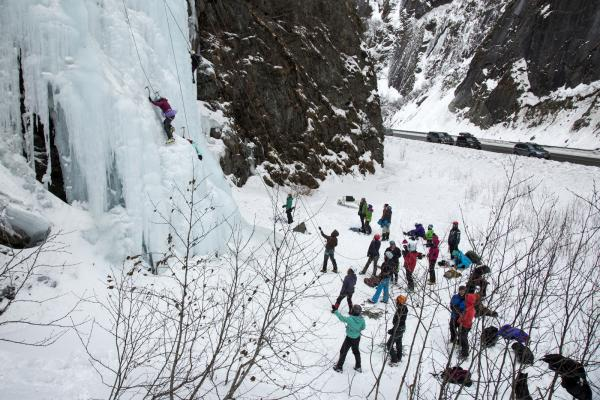 a group of people watching an ice climber ascend a frozen waterfall