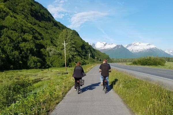 a couple rides bikes on a scenic bike path