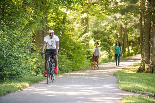 Man riding bike and women walking along wooded rail trail