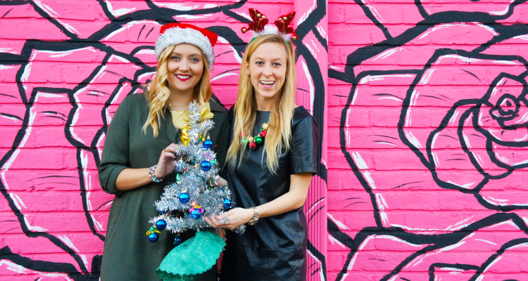 Natalie and Anastasia of It's Not Hou It's Me in front of pink mural holding a small Christmas tree in Houston