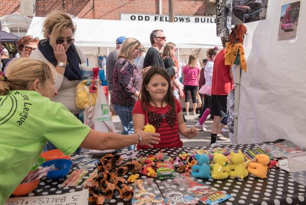 Girl plays a game at a Harvest Homecoming booth.