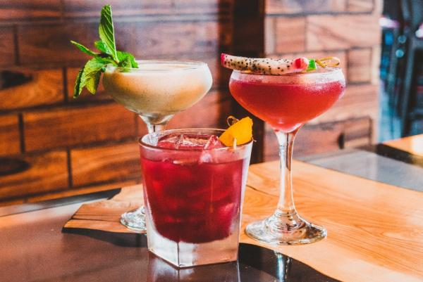 Three cocktails sit on a wooden serving plate in front of a brick wall at Brick & Bourboun in Maple Grove