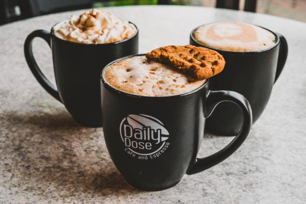 """Three coffee mugs filled with foamy drinks sit on a circular table in a triangular shape. The mug in front says """"Daily Dose Cafe and Espresso"""""""