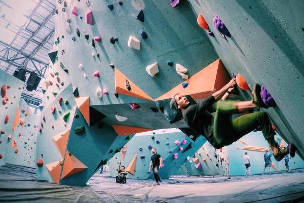 A female in the foreground climbs an indoor rock wall in a wide shot of the Minneapolis Bouldering Project