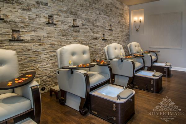 Photo of four open spa chairs in a room with a stone wall and wood flooring at Woodhouse Day Spa in Maple Grove, MN