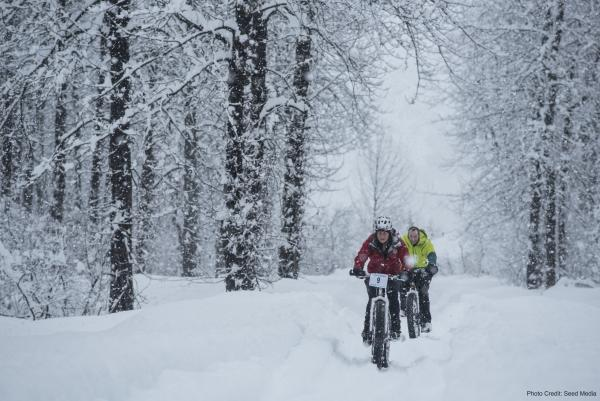 two fat bikers ride in snow through a Valdez forest