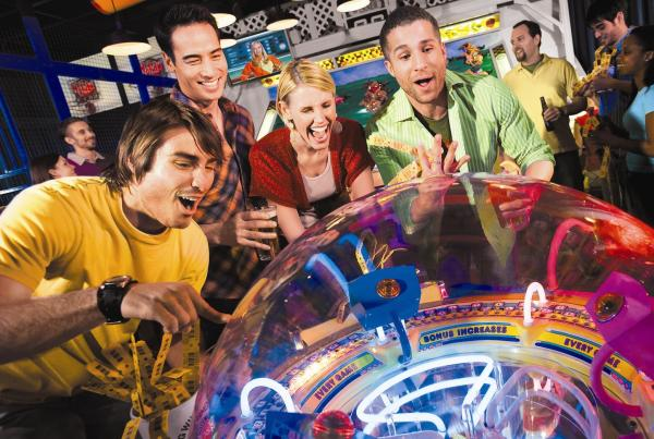 A group of adults looks on with excitement as a man plays an arcade game at Dave & Buster's