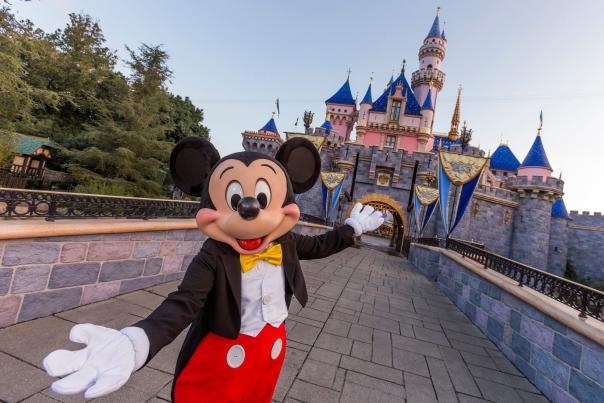 Image of Mickey Mouse with hands open, in a welcoming gesture, in front of Sleeping Beauty Castle at Disneyland Resort.