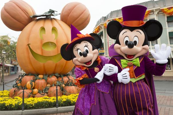 Image of Mickey and Minnie Mouse dressed up for halloween, standing in front of a Mickey-shaped giant pumpkin on Main Street U.S.A. inside Disneyland Park.