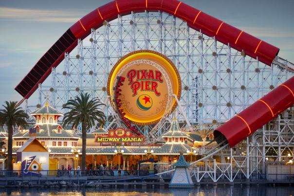 Image of Pixar Pier at Disney California Adventure at night time. Featured in the photo is the Incredicoaster and Toy Story Midway Mania attractions.