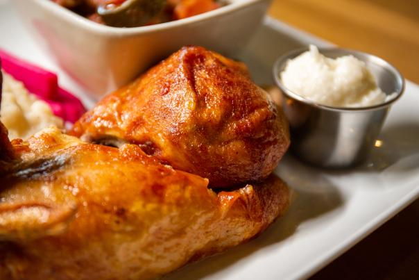 Image of chicken drumstick and chicken thigh served on a white plate with a small side of garlic sauce served in stainless steel metal container.