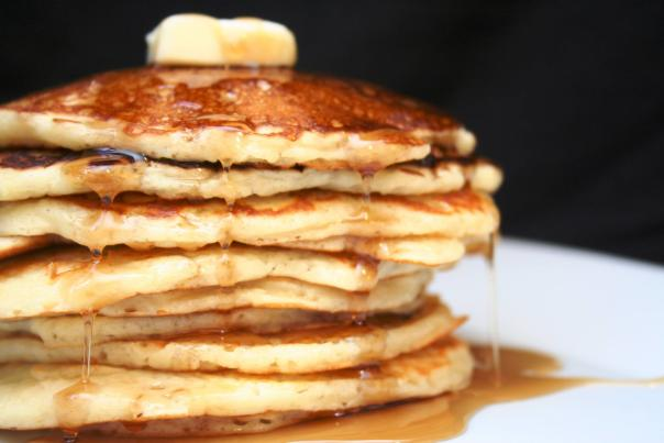 Image of a stack of pancakes covered in maple syrup and topped with a pat of butter.