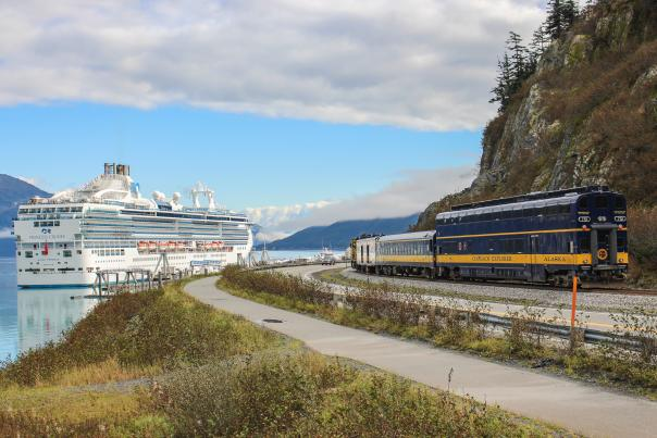 The Glacier Discovery train pulls into Whittier with a docked cruise ship