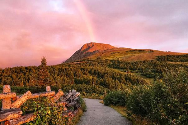 Flattop Mountain shines in the alpenglow with a rainbow in the background. Glen Alps Trailhead at Flattop one of the most accessible trails near Anchorage, Alaska.