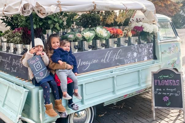 Kids sitting on Jojo the flower truck.