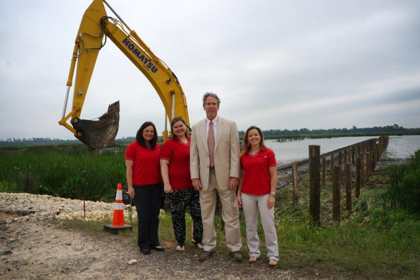 CVB Staff poses in front of construction site of Cattail Marsh Boardwalk